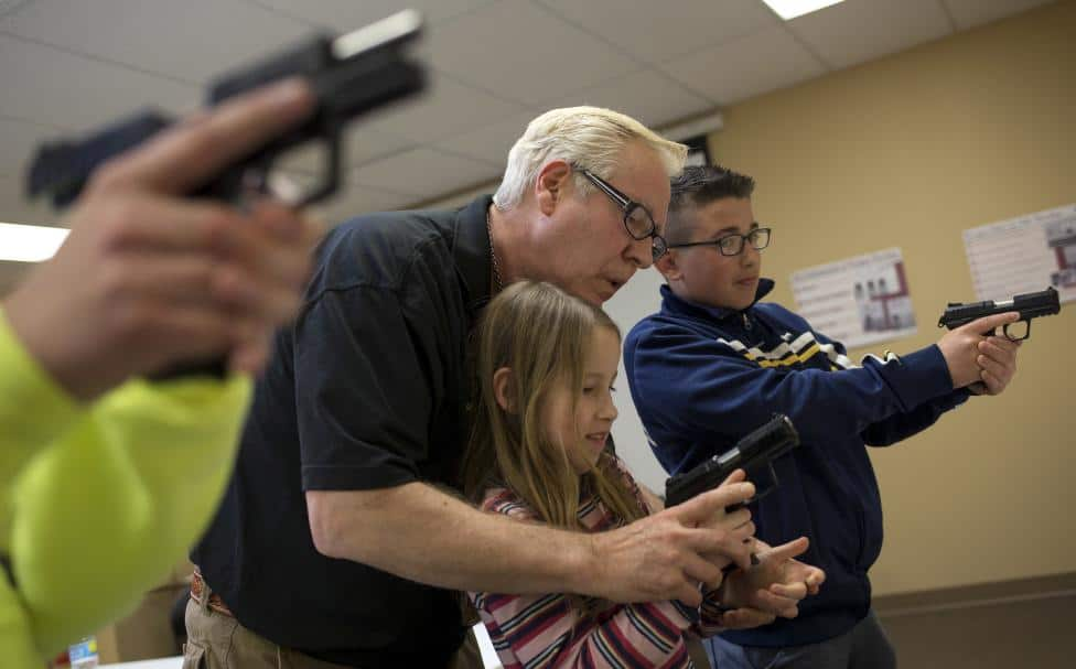 Instructor Jerry Kau shows student Joanna Zuber how to hold a handgun alongside Sam Minnifield during a Youth Handgun Safety Class at GAT Guns in East Dundee