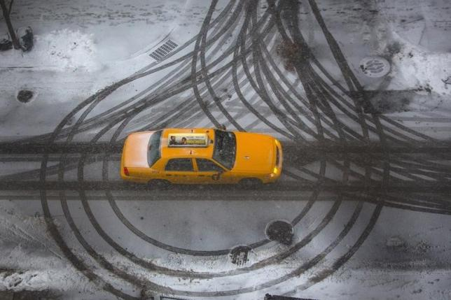 A taxi cab drives through tire marks in Brooklyn, New York January 25, 2014. REUTERS/Andrew Kelly